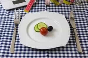 plastry ogórka, pomidor i oliwka na talerzu