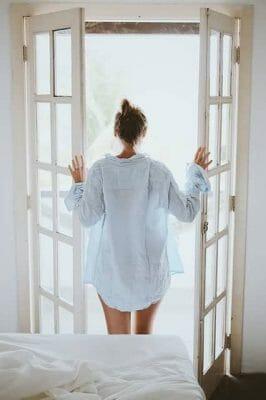 kobieta stoi przy otwartych drzwiach