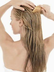 kobieta czesze umyte włosy
