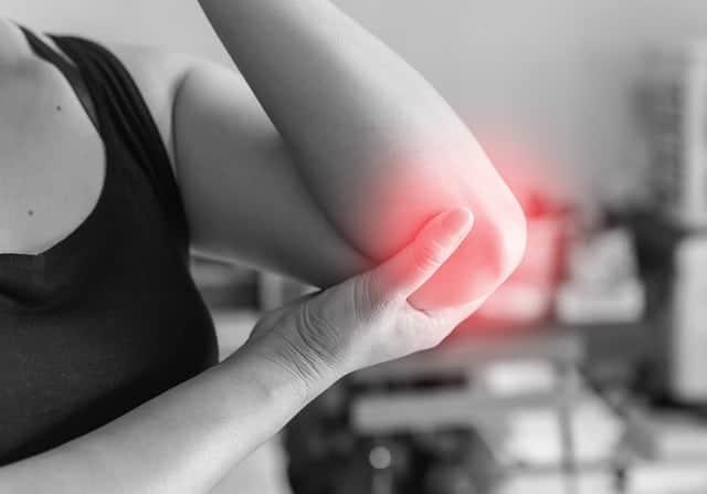 kobieta trzyma się za bolący łokieć