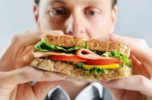 mężczyzna je kanapkę