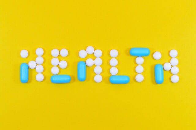 Napis zdrowie ułożony z tabletek i kapsułek