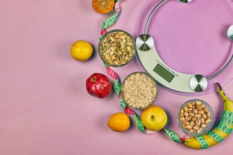 waga kuchenna i zdrowe dietetyczne jedzenie (ziarna, owoce)