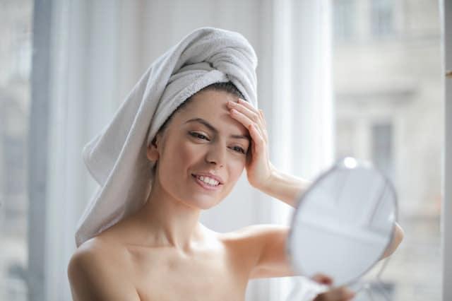 kobieta ogląda swoją twarz w lusterku