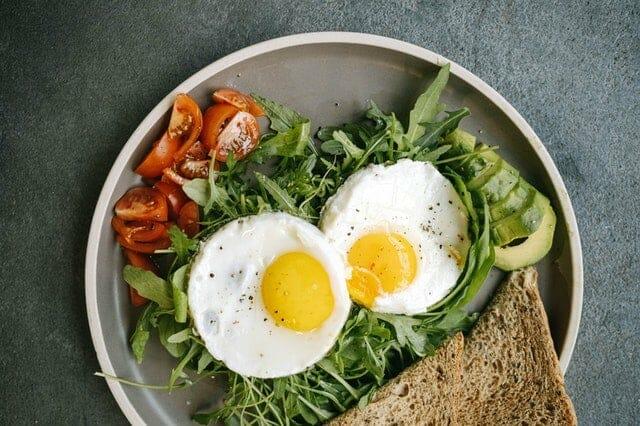 Dietetyczne danie - jajka sadzone, warzywa, chleb razowy