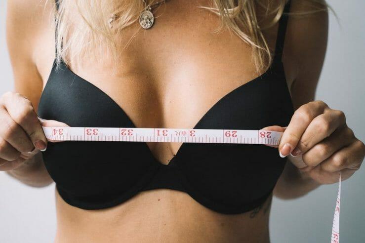 kobieta mierzy biust centymetrem