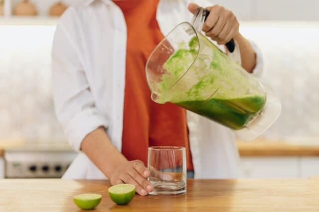 kobieta nalewa zielony koktajl do szklanki