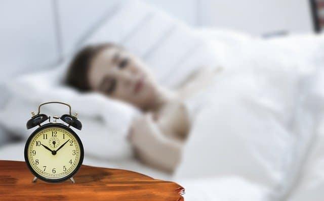 kobieta śpi, koło łóżka stoi budzik