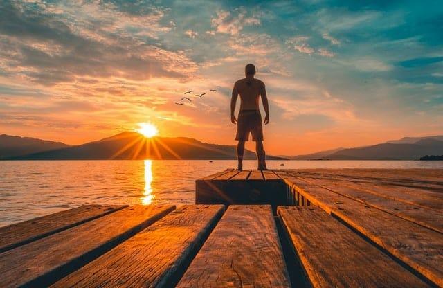 mężczyzna stoi na molo i obserwuje zachód słońca
