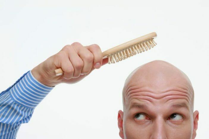 łysy mężczyzna ze szczotką do włosów w ręku