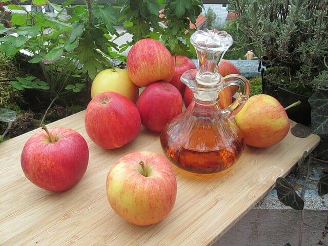świeże jabłka i flakon z octem jabłkowym na stole