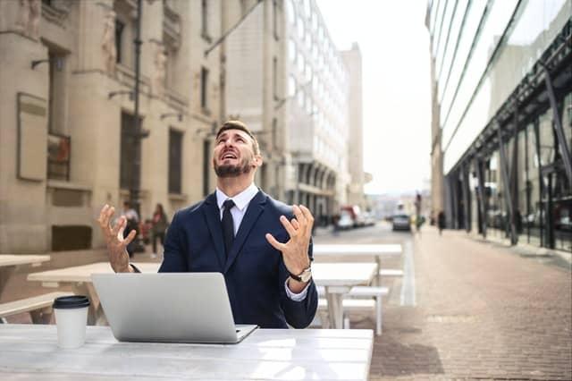 zdenerwowany mężczyzna pracujący przy laptopie