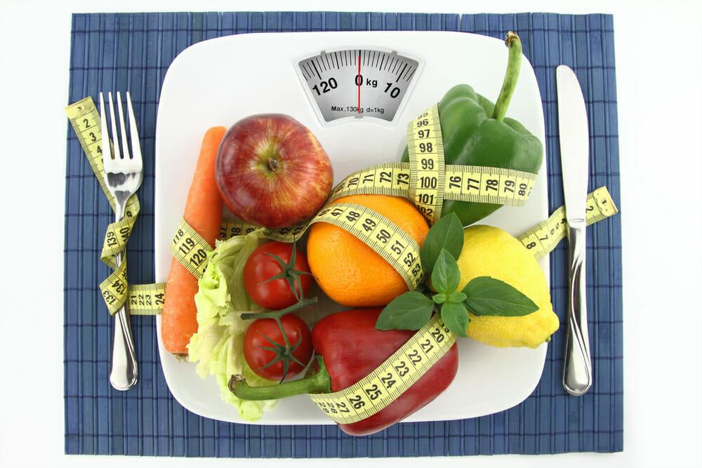 warzywa i owoce na talerzu obwiązane centymetrem