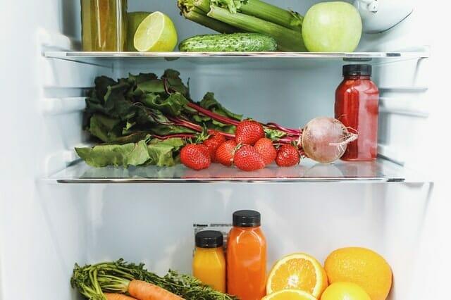 wnętrze lodówki, w środku warzywa, owoce i soki