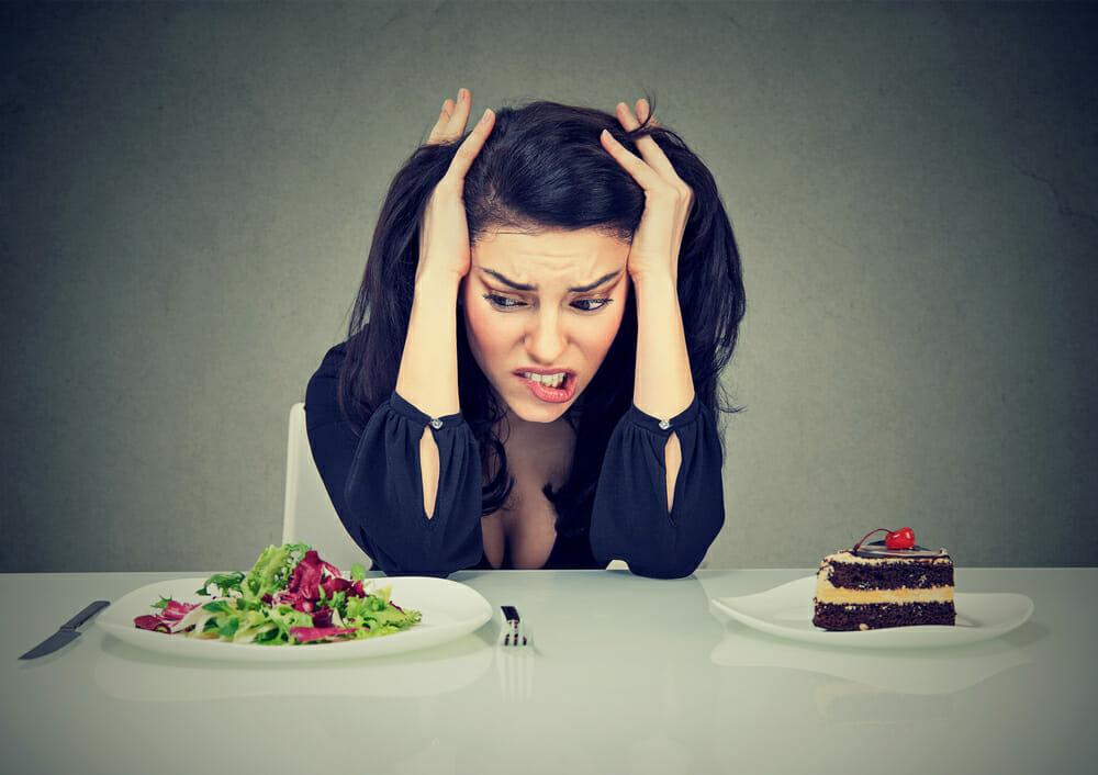 kobieta siedzi przy stole, na którym stoi talerz z ciastkiem i talerz z sałatką