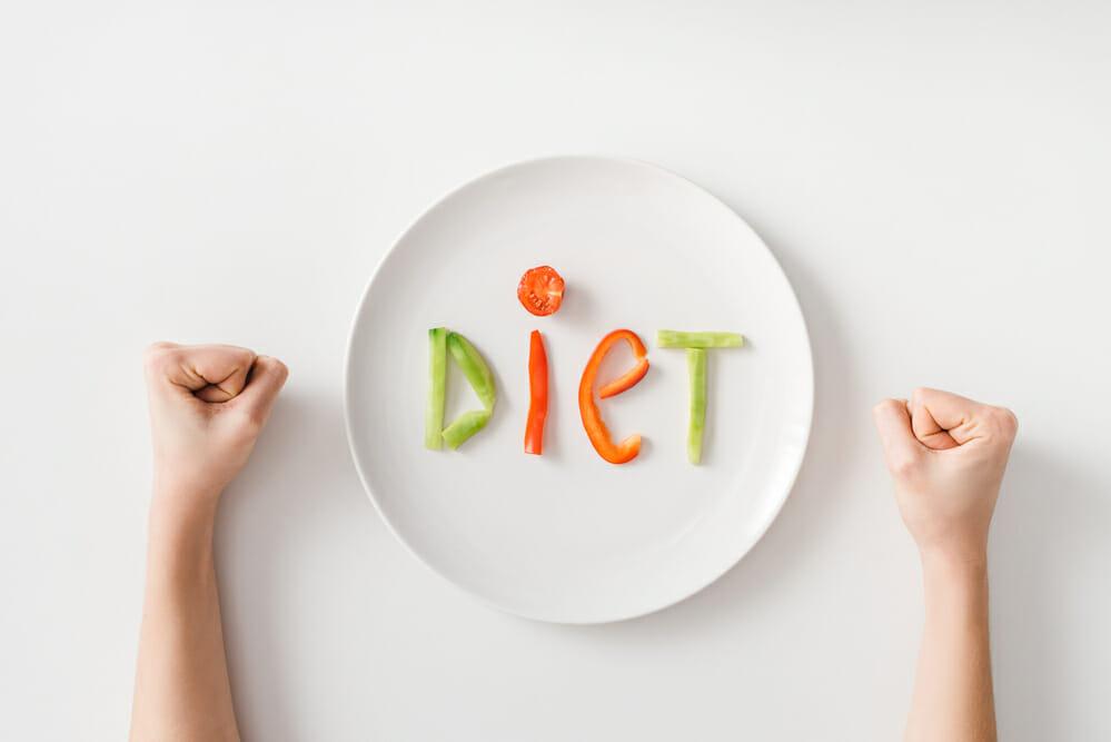 Zaciśnięte pięści, talerz, na talerzu kilka kawałków warzyw