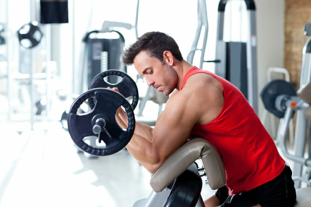 mężczyzna ćwiczy ze sztangą na siłowni