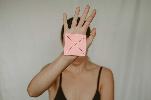 smutna kobieta trzyma przed sobą kartonik ze znakiem x