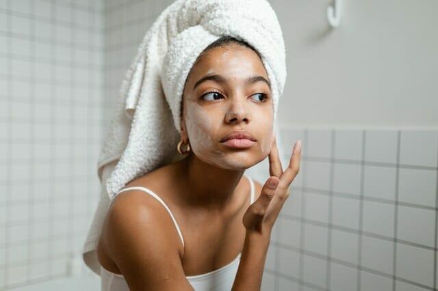 kobieta nakłada maseczkę na twarz