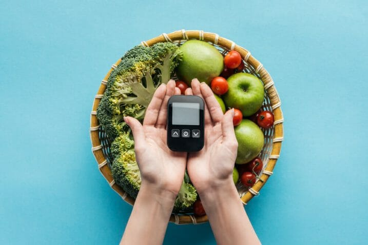 misa z warzywami i  owocami, obok glukometr trzymany w dłoniach