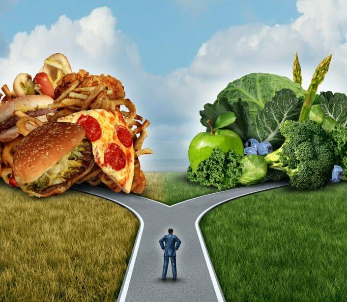 Mężczyzna zastanawia się, czy zjeść fast foody czy warzywa