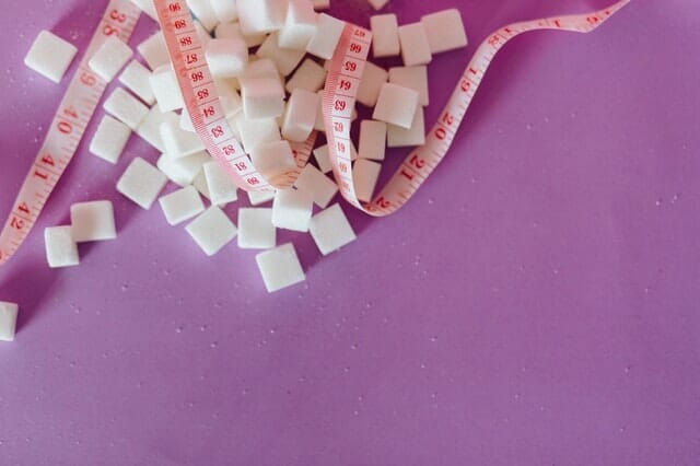 rozsypane kostki cukru, obok miarka